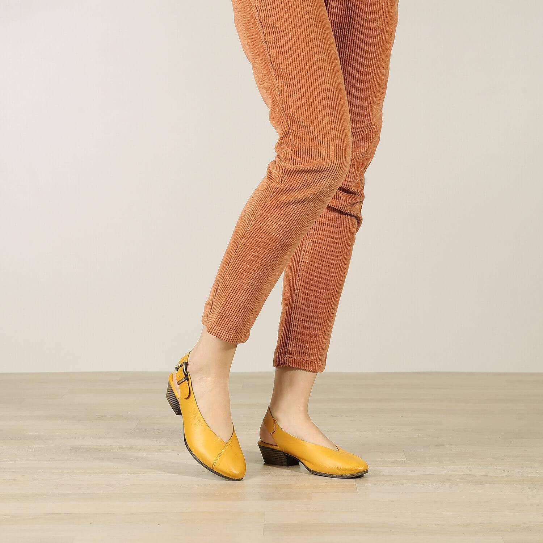 אישה נועלת נעלי סירה שטוחות בדוגמת מעטפת בצבע חרדל - דגם שי 84432