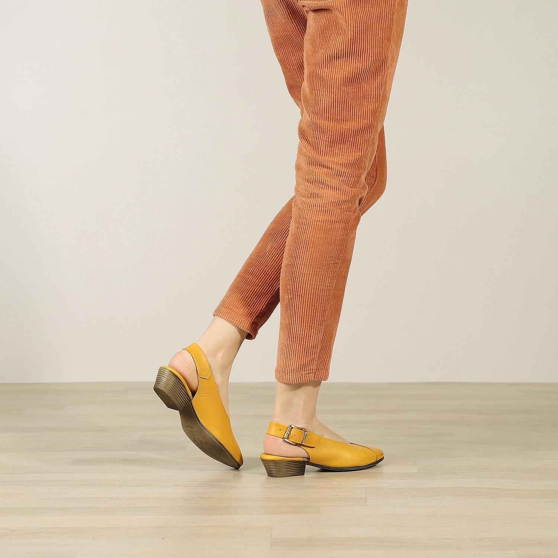 אישה נועלת נעלי סירה שטוחות בדוגמת מעטפת בגוון חרדל - דגם שי 84432