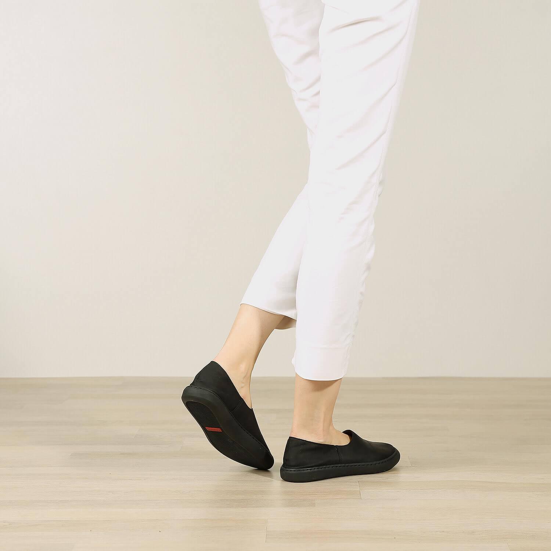 אישה נועלת נעלי בלרינה שטוחות בעיצוב ספורטיבי בצבע שחור - דגם אמי 8742